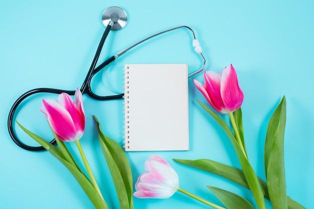 Tulipas cor de rosa e estetoscópio com bloco de notas em espiral com o texto do feliz dia dos médicos nele