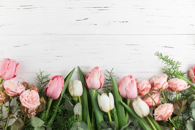 Tulipas cor de rosa e rosas em fundo de prancha de madeira