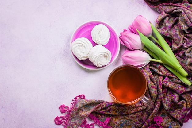 Tulipas cor de rosa e uma xícara de chá com marshmallows caseiros