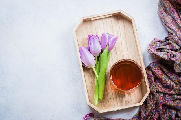 Tulipas cor de rosa e uma xícara de chá na bandeja de madeira