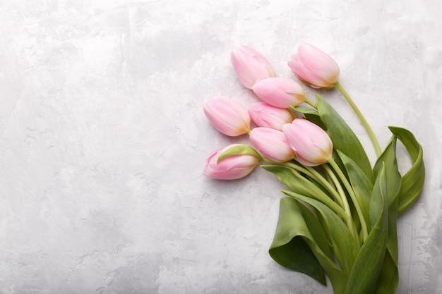 Tulipas cor de rosa em fundo de pedra cinza