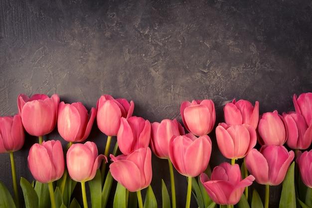 Tulipas cor de rosa em um fundo cinza escuro do grunge. copyspace.