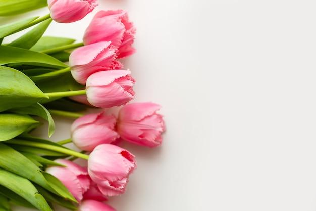 Tulipas cor de rosa em uma mesa branca