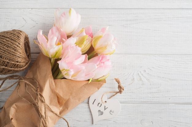 Tulipas cor de rosa frescas, cordéis e coração