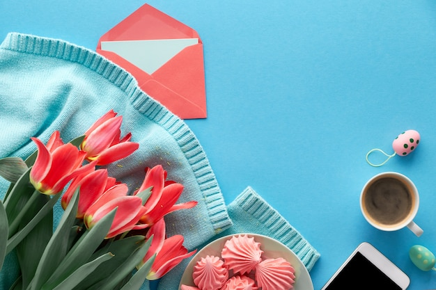 Tulipas cor de rosa na camisola de algodão, cartões e envelopes, telefone celular e café