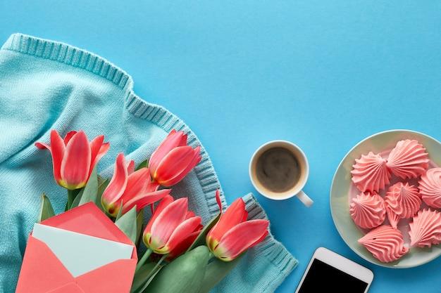 Tulipas cor de rosa na camisola de algodão cor de menta, cartões e envelopes, telefone celular, prato de marshmallow e xícara de café