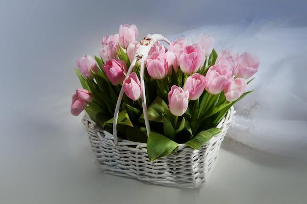 Tulipas cor de rosa na cesta com anéis de casamento em branco