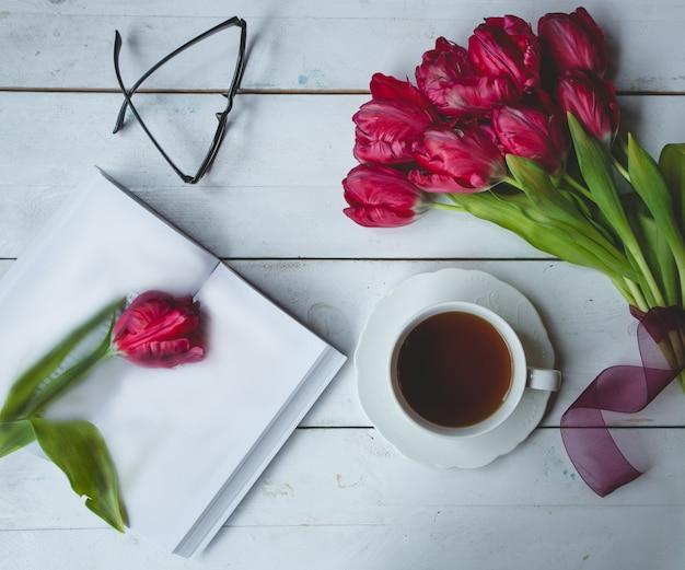 Tulipas da borgonha, copos, uma xícara de chá e um diário