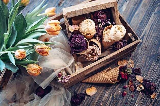 Tulipas da primavera cor laranja e sorvete em caixas de madeira. vista do topo
