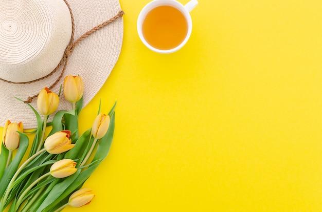 Tulipas de buquê vista superior sobre o fundo amarelo, chá e chapéu