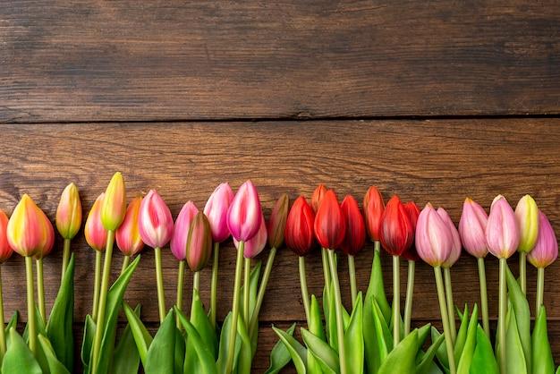 Tulipas de cores diferentes na mesa de madeira, quadro acima, copie o espaço