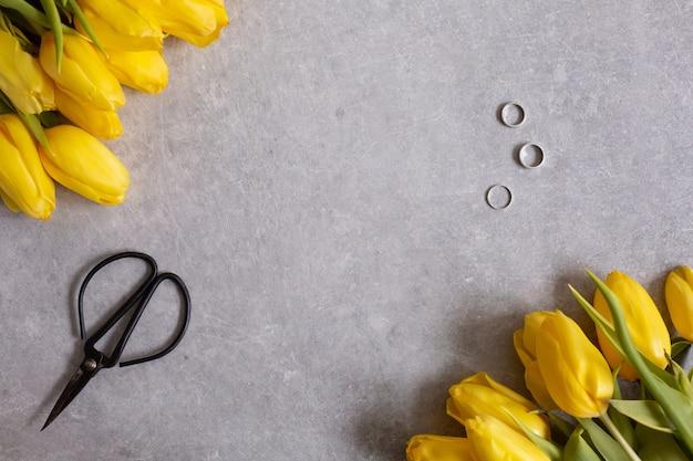 Tulipas de flores amarelas e tesoura vista superior