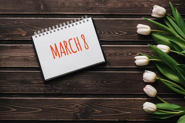 Tulipas de flores brancas em tábuas de mesa de madeira marrom. cartão com letras 8 de março