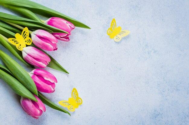 Tulipas de primavera e papel borboleta no fundo para o dia das mães