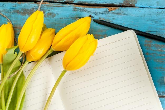 Tulipas e caderno na mesa azul