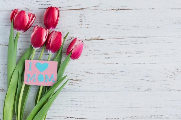 Tulipas e cartão para o dia de mãe no fundo de madeira