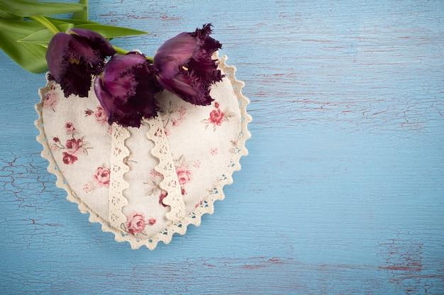 Tulipas e coração no fundo de madeira azul