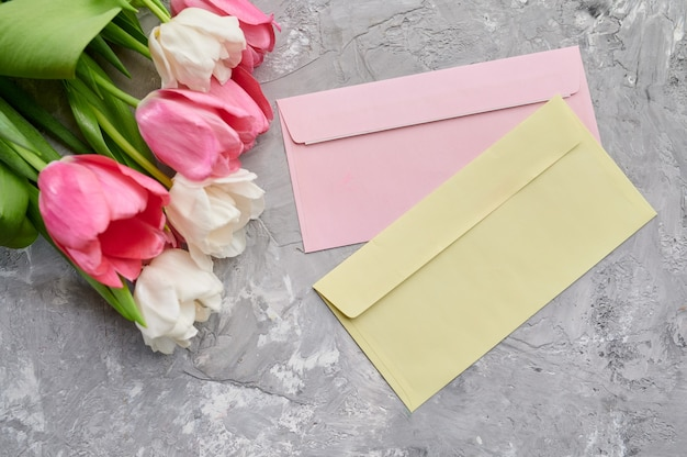 Tulipas e envelopes em fundo cinza grunge