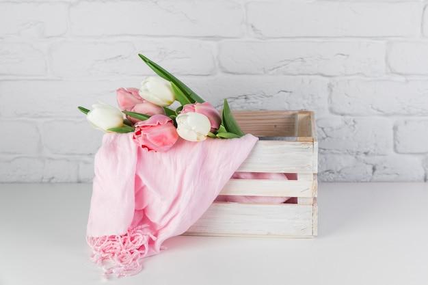 Tulipas e lenço rosa dentro da caixa de madeira na mesa contra a parede de tijolos brancos
