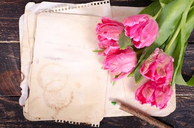 Tulipas e papel cor-de-rosa do vintage, lápis em um fundo de madeira. espaço livre para o seu texto.