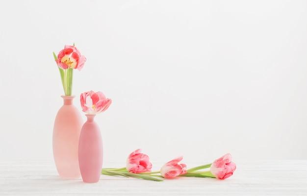 Tulipas em um vaso rosa na mesa branca