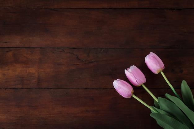 Tulipas em uma superfície de madeira escura. vista plana, vista superior