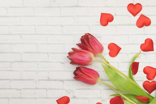 Tulipas flores vermelhas e corações em um fundo branco da parede de tijolo