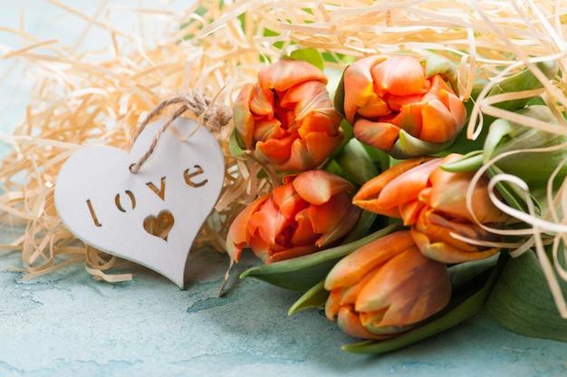 Tulipas laranja com coração de madeira