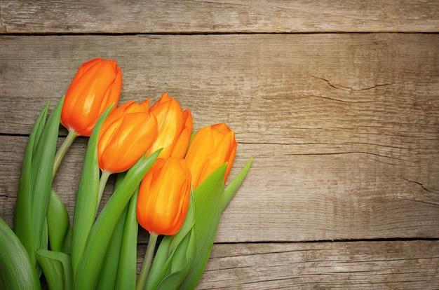 Tulipas laranja em fundo de madeira.