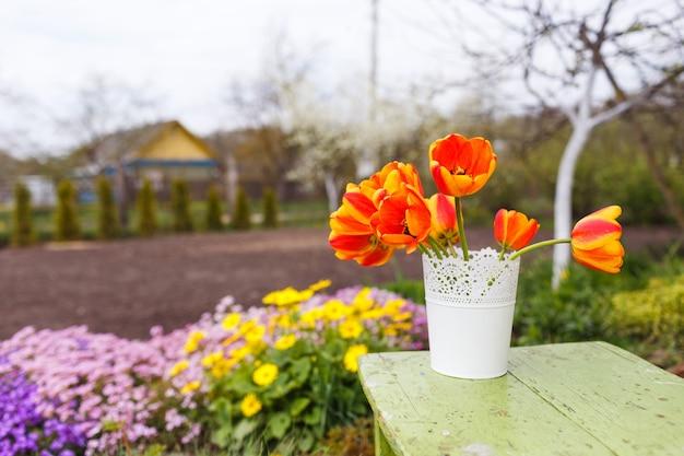 Tulipas laranja em um vaso sobre a mesa no contexto da natureza.