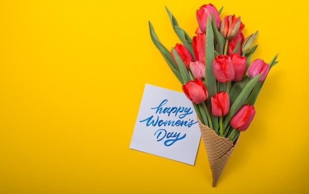Tulipas lindas vermelhas em um cone de waffle de sorvete com cartão de tinta em um fundo de cor amarela. idéia conceitual de um presente de flor. humor de primavera