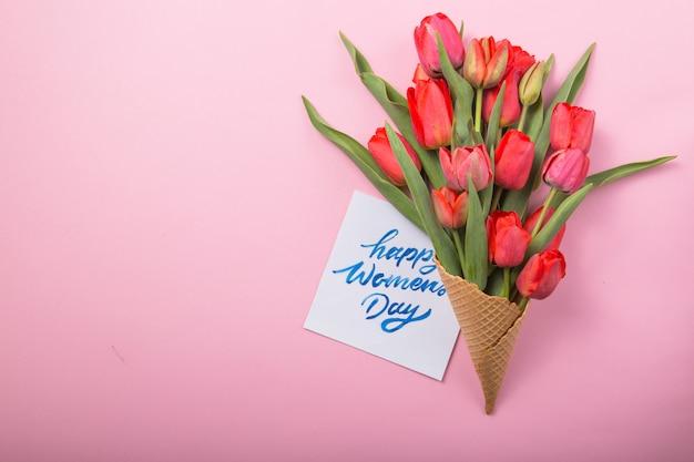 Tulipas lindas vermelhas em um cone de waffle de sorvete com cartão em um fundo de cor. idéia conceitual de um presente de flor. humor de primavera