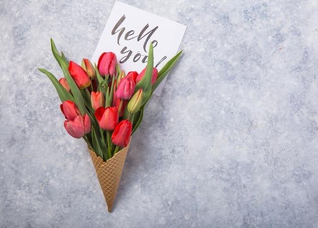 Tulipas lindas vermelhas em um cone de waffle de sorvete com cartão olá você, sobre um fundo de concreto. idéia conceitual de um presente de flor. humor de primavera