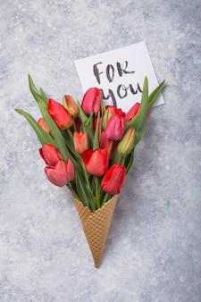 Tulipas lindas vermelhas em um cone de waffle de sorvete com cartão para você, sobre um fundo de concreto. idéia conceitual de um presente de flor. humor de primavera