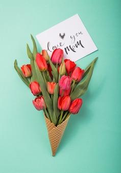 Tulipas lindas vermelhas em um cone de waffle de sorvete com cartão te amo mãe, sobre um fundo de cor azul. idéia conceitual de um presente de flor. humor de primavera