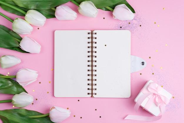 Tulipas pastel com caderno e caixa de presente na mesa-de-rosa com estrelas, copie o espaço
