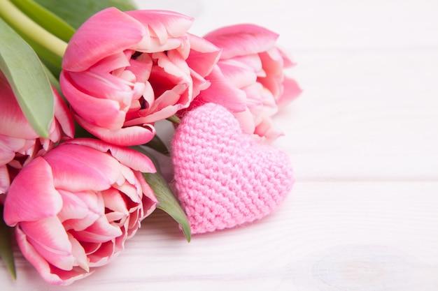 Tulipas rosa delicadas em um branco de madeira