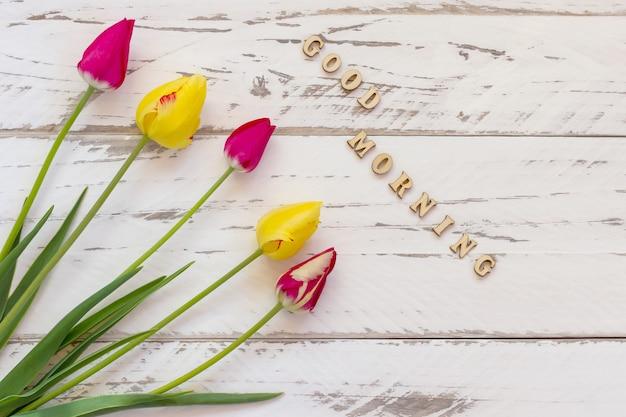 Tulipas rosa e amarelas em background de madeira. cartão de primavera com espaço de cópia. citação de bom dia.