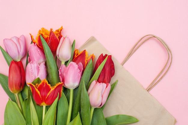 Tulipas rosa e vermelhas e um saco de papel em uma rosa