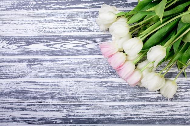 Tulipas rosa muito brancas e brancas em branco, cinza de madeira backgrou