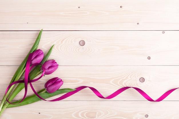 Tulipas roxas com fita na parede de madeira branca