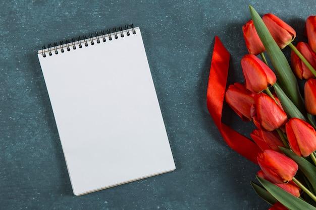 Tulipas vermelhas, caderno em azul, cartão postal em branco, férias de primavera, dia das mães. copie o espaço.