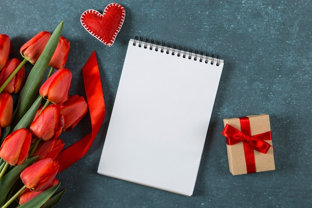 Tulipas vermelhas, coração, caderno e presente em azul, cartão postal em branco, férias de primavera, dia das mães. copie o espaço.