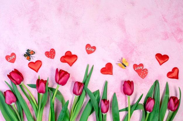 Tulipas vermelhas, corações vermelhos e borboletas esvoaçantes em um plano de fundo rosa texturizado com uma cópia do espaço