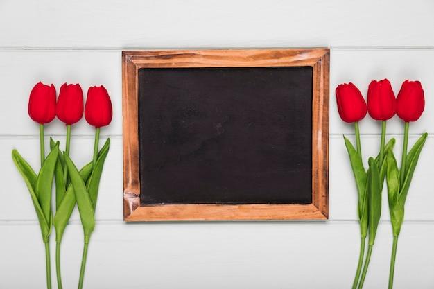 Tulipas vermelhas de vista superior ao lado do quadro