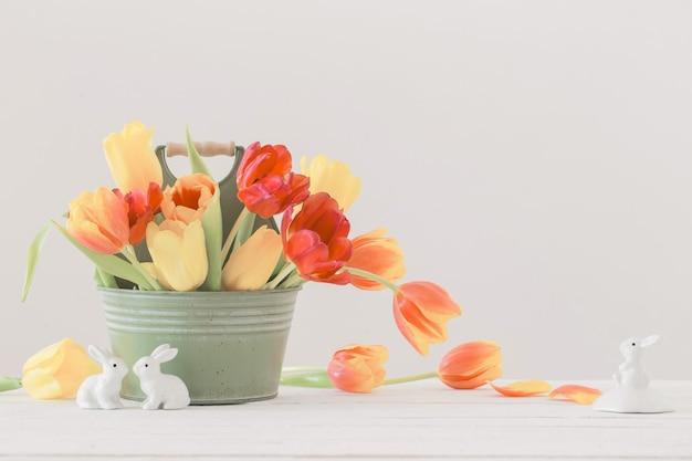 Tulipas vermelhas e amarelas em um balde e coelho de cerâmica em fundo branco