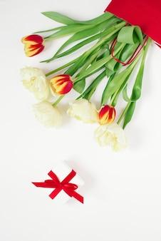 Tulipas vermelhas e amarelas em uma sacola vermelha e um presente em um fundo branco com espaço de cópia.