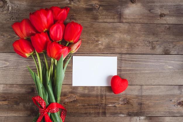 Tulipas vermelhas e cartão na mesa de madeira, vista superior
