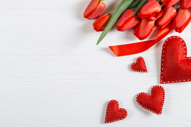 Tulipas vermelhas e corações na mesa branca, em branco para cartões postais. copie o espaço.