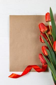 Tulipas vermelhas e modelo de papel ofício no azul, em branco para um cartão postal para o dia do professor. copie o espaço.